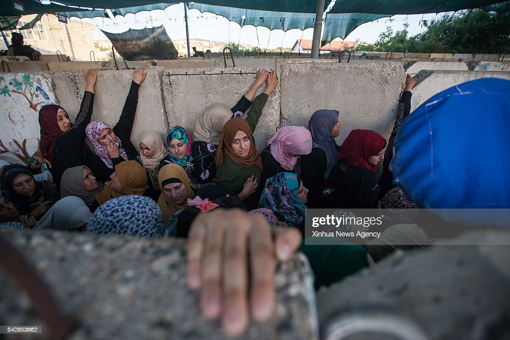 Palestinians are seen at an Israeli checkpoint as they make their way to attend the third Friday prayer of the holy fasting month of Ramadan in Jerusalem's al-Aqsa mosque, in the West bank city of Bethlehem on June 24, 2016.
