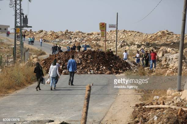 Palestinians are seen on the road blocked by Israeli soldiers as Israeli forces siege around the hometown of a Palestinian man Monir alAbed who...