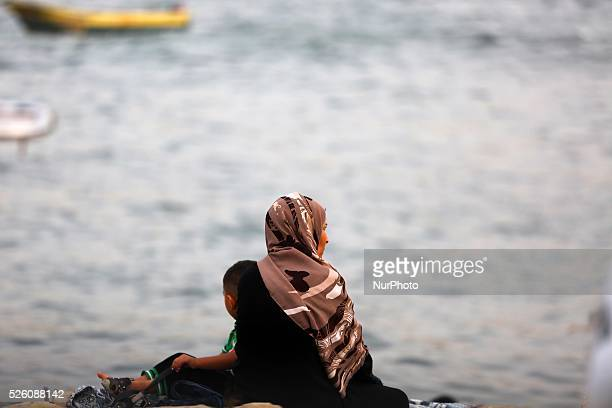 Palestinians are sitting on a Gaza beach on a hot day on 10 september 2015
