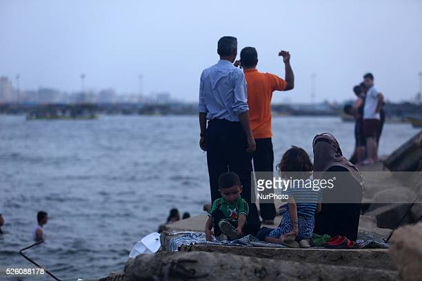 Palestinians are sitting on a Gaza beach on a hot day