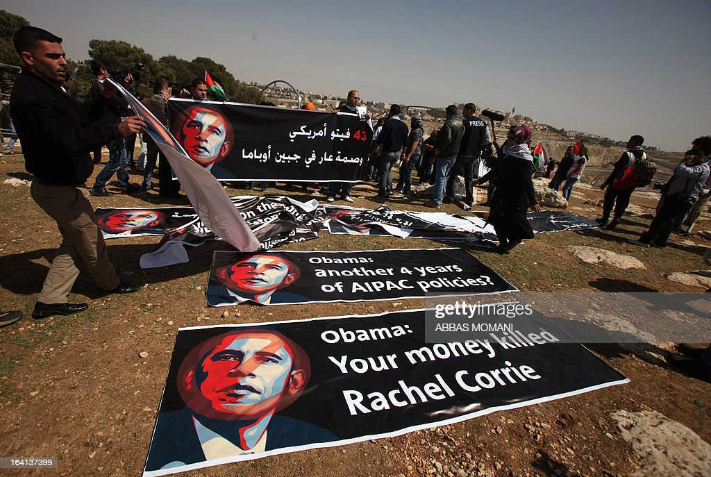 Palestinians arrange banners with the image of US President Barak Obama at a 'tented village' set up close to Israel's largest Jewish settlement of Maale Adumin on the outskirts of Jerusalem where the US president is visiting on March 20, 2013, on the first day of his three day visit.