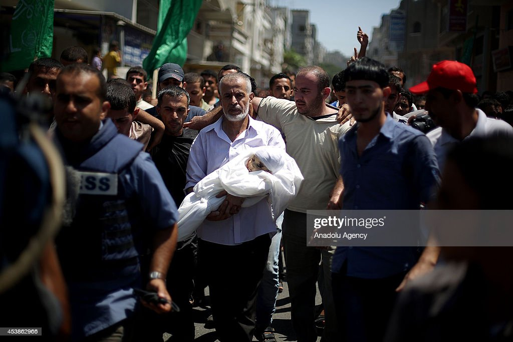 Palestinians attend the funeral ceremony of Hamas's military commander Mohammed Deif's son sevenmonthold Ali Deif and wife 27yearold Widad Deif at...