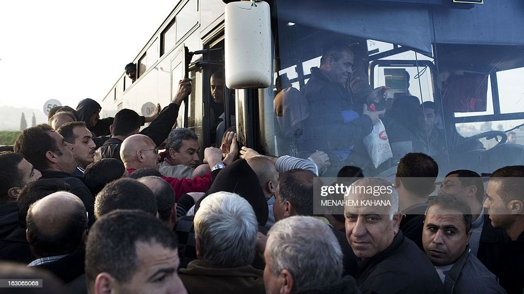 Palestinians board a bus as a new line is made available by Israel to take Palestinian labourers from the Israeli army crossing Eyal, near the West Bank town of Qalqilya, into the Israeli city Tel Aviv, on March 4, 2013.Thousands of Palestinians enter Israel to work every day after receiving permits, many of them in private vans. The new line will not be available for Jewish settlers.