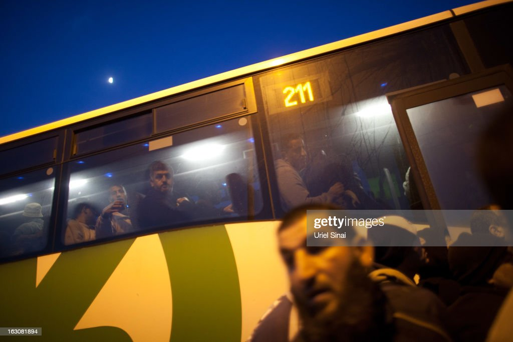 Palestinians board a bus as a new line is made available by Israel to take Palestinian labourers from the Israeli army crossing of Eyal, near the West Bank town of Qalqilya, into the Israeli cities, on March 4, 2013. at Eyal crossing, West Bank. The new line service to ferry Palestinian workers from the West Bank to Israel, encouraging them to use it instead of traveling with Israeli settlers on a similar route.