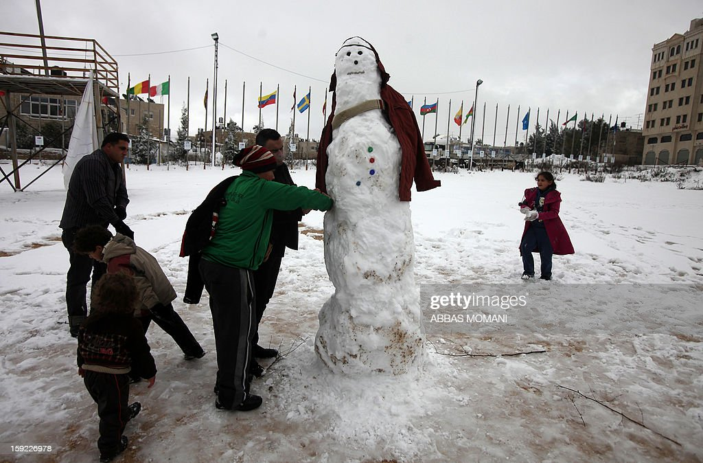 Palestinians build a snowman in the West Bank city of Ramallah on January 10, 2013. Abnormal storms which have blasted the Middle East with rain, snow and hail have claimed at least 11 lives in a region accustomed to temperate climates. AFP PHOTO/ABBAS MOMANI
