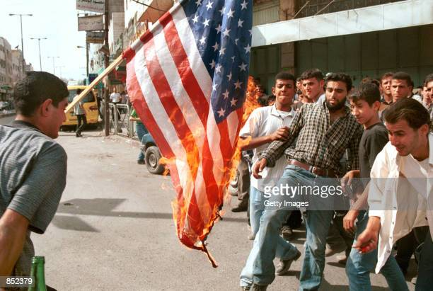 Palestinians burn an American flag during a riot October 3 2000 in the West Bank city of Hebron Jerusalem Clashes between Israeli troops and...