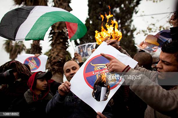 Palestinians burn posters with the logo of AlJazeera TV station as Israeli police Restricts Palestinian Access To Friday Prayers at the old city on...