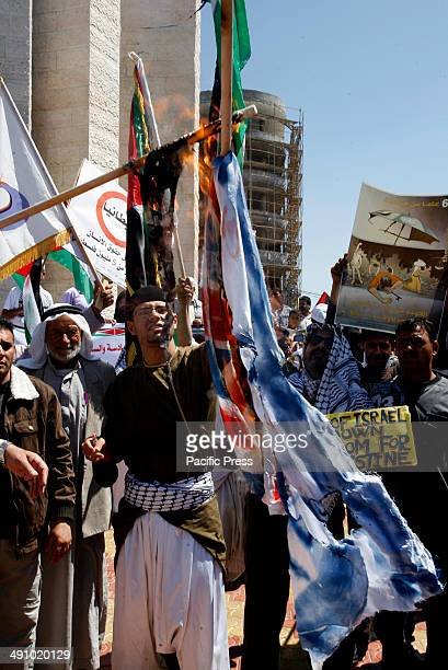 Palestinians burn replicas of the Israeli and British flags during a rally ahead of the 66th anniversary of Nakba in Rafah in the southern Gaza Strip...