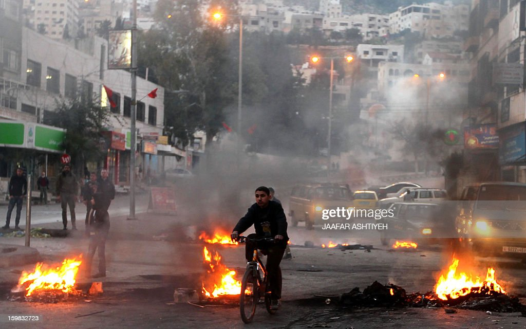Palestinians burn tires at the entrance to the Balata refugee camp, close to the northern West Bank city of Nablus, on January 21, 2013, as they call for the release of several gunmen arrested two days ago by Palestinian security.