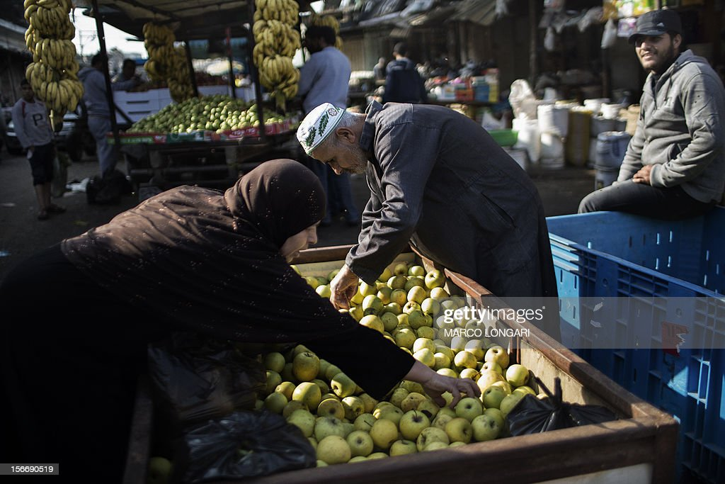 Palestinians buy apples from a street vendor at a central market in Gaza City on November 19, 2012. Food prices have started to rise in the Gaza Strip due to the lack of fresh supplies as scarce produce is met with more demands by the residents of the Palestinian coastal enclave, due to the ongoing unrest with Israel.