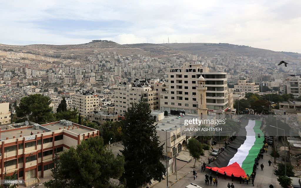 Palestinians carry a 100 meter long Palestinian flag during a rally in the West Bank city of Nablus on November 14 on the 10th anniversary to...