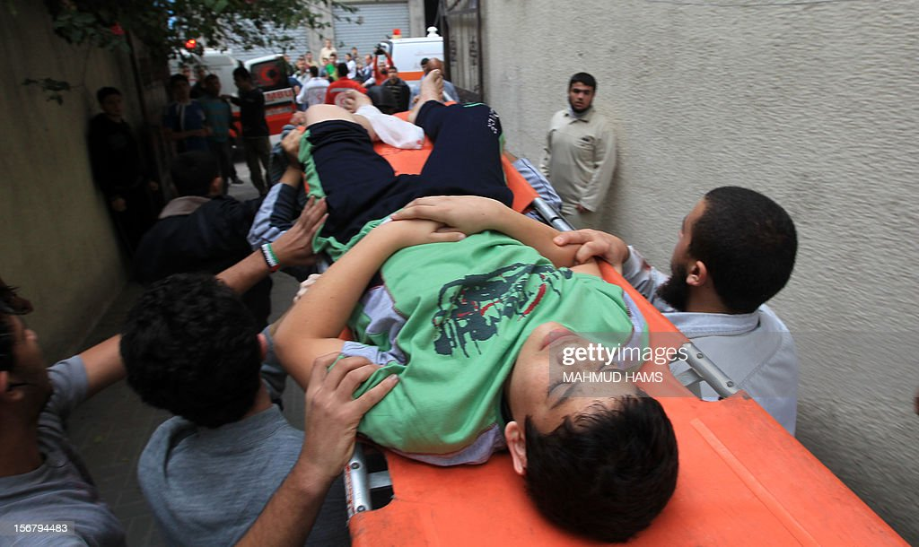 Palestinians carry a boy wounded after an Israeli strike on the building housing AFP's offices in Gaza city, according to Hamas health officials, on November 21, 2012. The Israeli military had no immediate comment on the strike, which came less than 24 hours after Israeli warplanes carried out a first raid on the building.