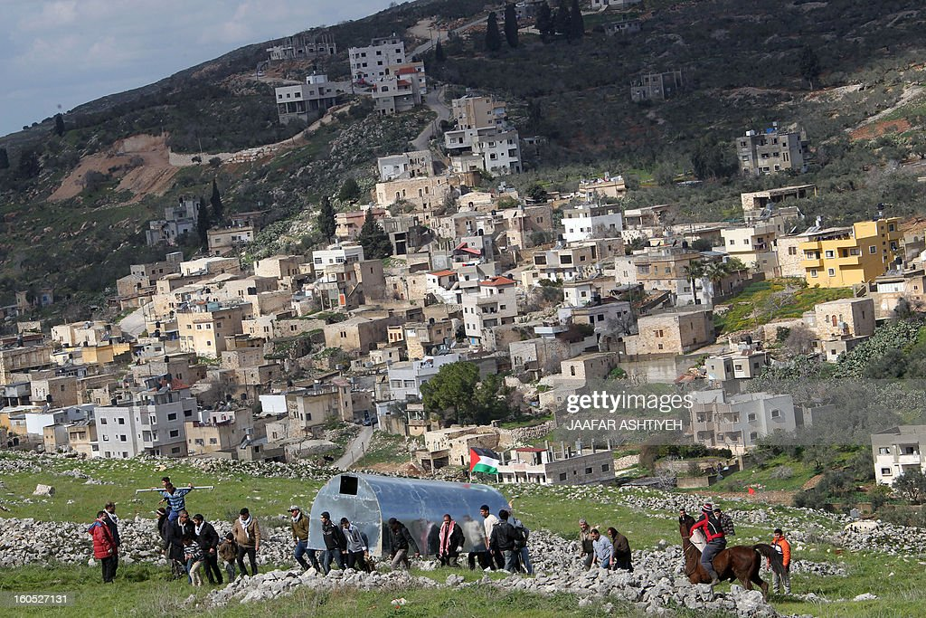 Palestinians carry a metal box as they set up a new camp to protest against Jewish settlements near the West Bank village of Burin on February 2, 2013. An AFP correspondent said the Israeli army used tear gas and violence to remove hundreds of people who had set up four temporary huts and three tents near Burin, south of Nablus in the occupied West Bank, in a third attempt at the novel form of protest against Jewish settlements. AFP PHOTO /JAAFAR ASHTIYEH