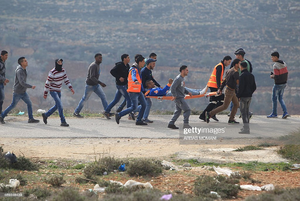 Palestinians carry a protestor on a stretcher who was injured during clashes between Israeli security forces and youths from the Palestinian refugee camp of al-Jalazun, during a weekly demonstration against the nearby West Bank Jewish settlement of Beit El on February 14, 2014.