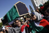 Palestinians carry a simbolic coffin decorated with the Italian flag during a ceremony to mourn and denounce the kidnapping and killing of Italian...