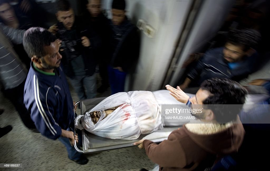Palestinians carry a stretcher with the body of Ibrahim Mansur, a Palestinian who was shot dead by Israeli troops, at the morgue of al-Shifa Hospital in Gaza city on February 13, 2014. 'Ibrahim Suleiman Mansur died after he was shot by Israeli occupation forces while he was collecting gravel... east of Gaza City' ministry spokesman Ashraf al-Qudra told AFP.