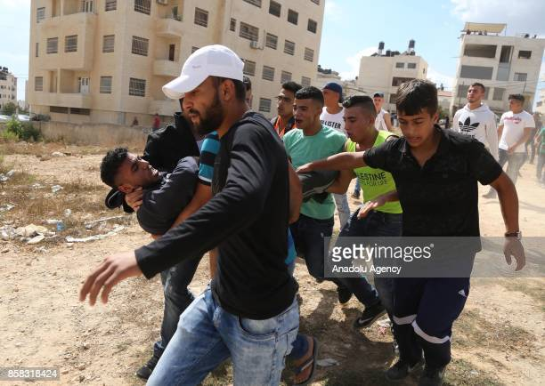 Palestinians carry a wounded man after a clash between Israeli security forces and Palestinians following the Israeli authorities organised a raid...