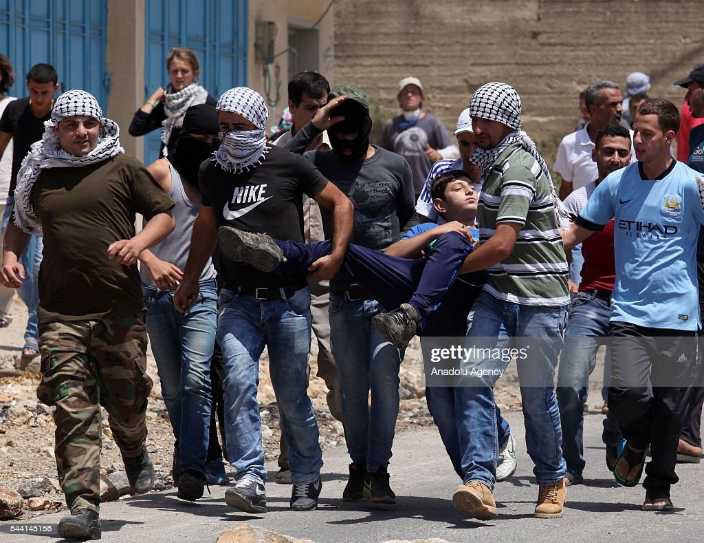 Palestinians carry a wounded person during the protest against land expropriations by Israeli government at the village of Kafr Qaddum in the city of Nablus on the West Bank on July 1, 2016.