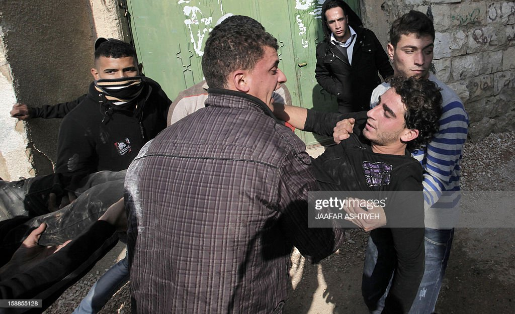 Palestinians carry an injured man during clashes in the West Bank village of Tamoun, near Jenin on January 1, 2013. Israeli troops wounded dozens of Palestinians in clashes in a West Bank village after the discovery of a small commando force disguised as Arabs brought a crowd of stone-throwing villagers onto the streets, Palestinians said. AFP PHOTO / JAAFAR ASHTIYEH