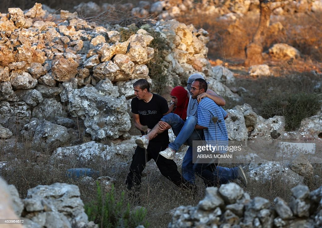 Palestinians carry an injured man who was shot by Israeli security forces during clashes in the West Bank village of Silwad, near Ramallah, following a demonstration in support of the Hamas militants' resistance in the Gaza Strip and against the killing of children by Israeli strikes on the Palestinian enclave on August 22, 2104. Hamas gunmen executed 18 people accused of collaborating with Israel in Gaza City as Palestinian mortar fire killed a four-year-old Israeli boy on Day 46 of a devastating war.