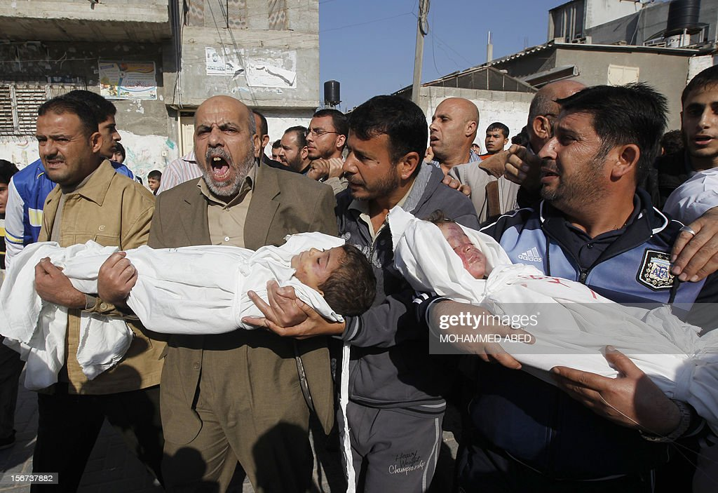 Palestinians carry the bodies of brothers Suhiab, 2-years-old, and Mohammed Hejazi, 4-years-old, during their funeral in the northern Gaza Strip area of Beit Lahia, on November 20, 2012. Four members of the Hejazi family were killed in the Israeli air strike in Gaza, the Hamas Health Ministry said. AFP PHOTO/MOHAMMED ABED