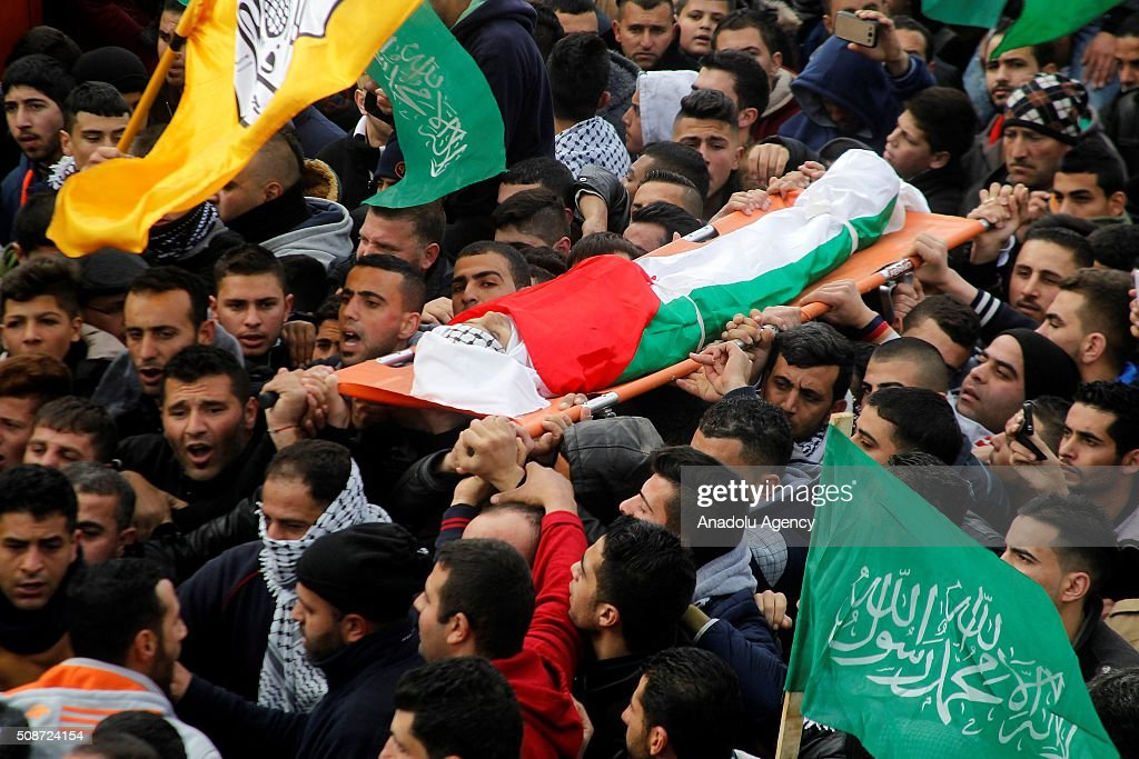 Palestinians carry the body of 17 year-old Palestinian Heisem Al-bao who has been killed by Israeli soldiers, during a funeral ceremony at Halhul village in Hebron, West Bank on February 6, 2016.