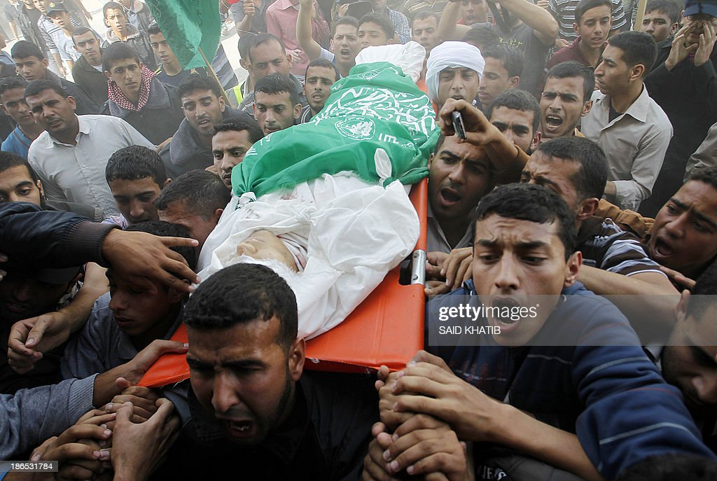 Palestinians carry the body of a local commander of Hamas's military wing Rabieh Barikeh, one of the four Hamas militants killed overnight in a firefight with Israeli troops, during his funeral on November 1, 2013 in Khan Yunis in the southern Gaza Strip. Barikeh was killed by tank fire, Palestinian officials said, while the Israeli army said five of its soldiers were wounded by an explosive device. The Israeli military said the fighting erupted when an explosive device went off as troops were clearing a tunnel from the Gaza Strip into Israel, allegedly to be used as a springboard for militant attacks.