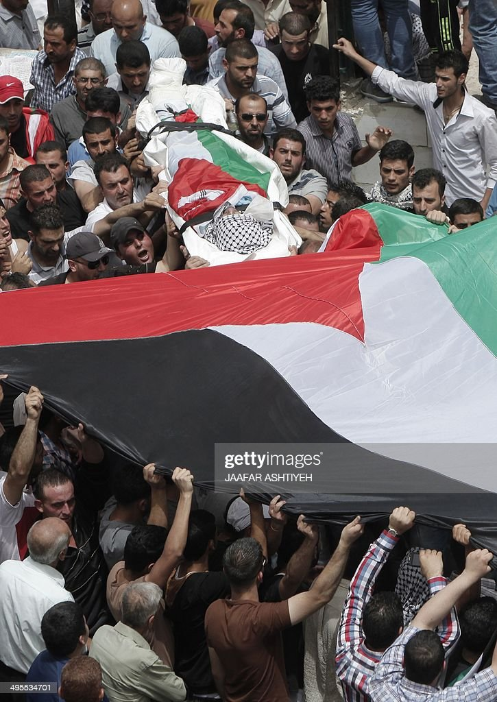 Palestinians carry the body of Alaa Awdeh, draped in the Palestinian flag, during his funeral procession in the West Bank village of Hawara on June 4, 2014, after he was killed at the Tapuach junction in the northern West Bank late on June 2. Israeli security forces killed Awdeh after he shot and wounded a border guard in the northern West Bank, the army said.