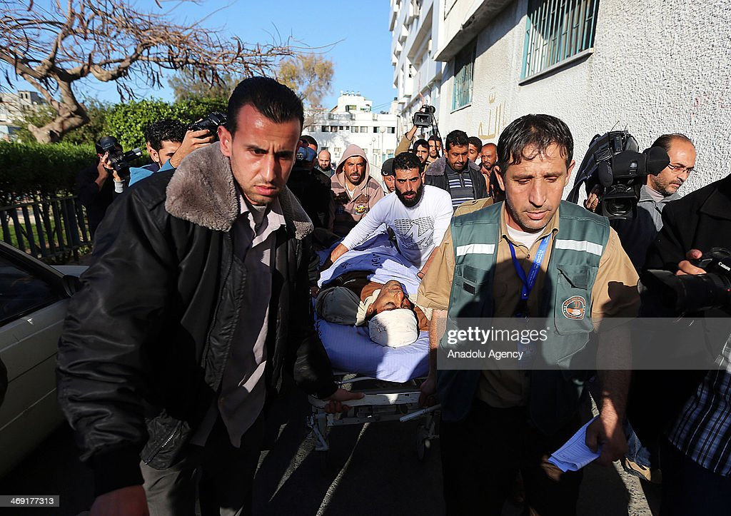 Palestinians carry the body of Ibrahim Mansour, 26, shot dead in the head by Israeli forces, at a local hospital in Gaza City, on February 13, 2014. A Palestinian man died Thursday after Israeli forces stationed near a border fence east of Gaza City opened fire on a group of Palestinian workers, a Palestinian official said.