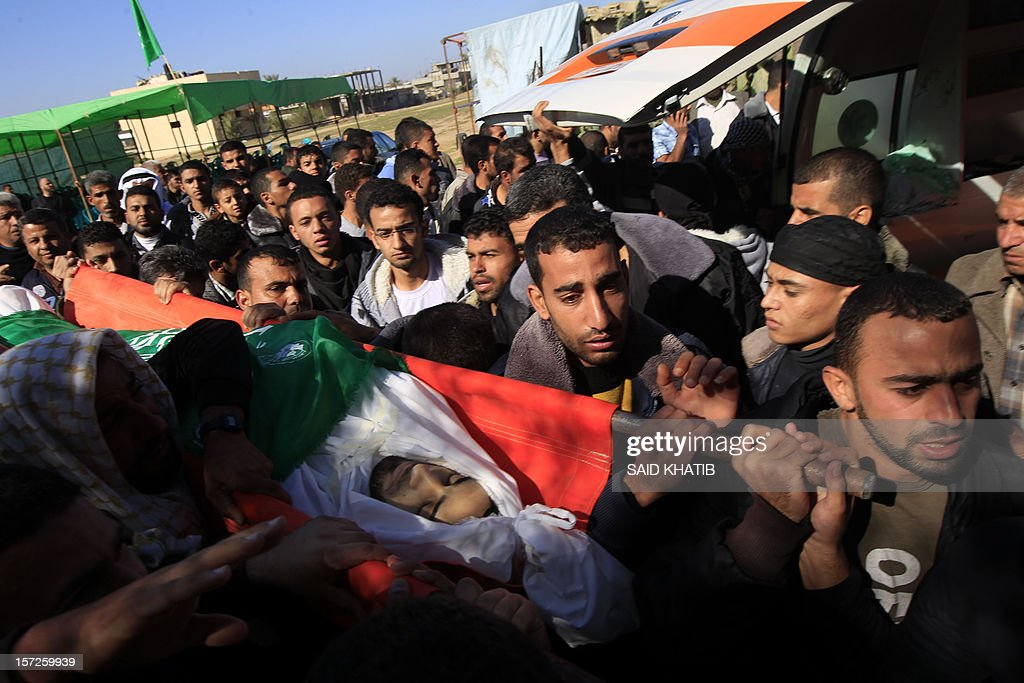 Palestinians carry the body of Mahmoud Jarghoun, 21, during his funeral in the town of Rafah in the southern Gaza Strip on December 1, 2012. One Palestinian died and another was wounded when an Israeli missile fired days earlier exploded in the north of the Gaza Strip, an emergency services spokesman said.