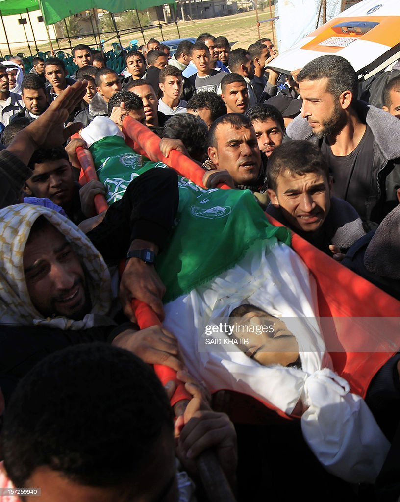 Palestinians carry the body of Mahmoud Jarghoun, 21, during his funeral in the town of Rafah in the southern Gaza Strip on December 1, 2012. One Palestinian died and another was wounded when an Israeli missile fired days earlier exploded in the north of the Gaza Strip, an emergency services spokesman said. AFP PHOTO/ SAID KHATIB