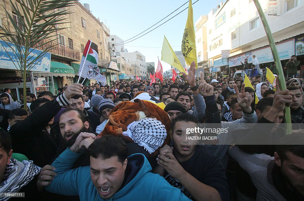 Palestinians carry the body of Odai Darwish, 21, during his funeral on January 13, 2013, in the village of Duma, the day after he was shot dead by Israeli soldiers as he tried to sneak from the occupied West Bank, south of the city of Hebron, into the Jewish State to get to a job, Palestinian officials told AFP. The Israeli military confirmed that a border shooting took place but did not know the extent of the man's injuries. AFP PHOTO / HAZEM BADER