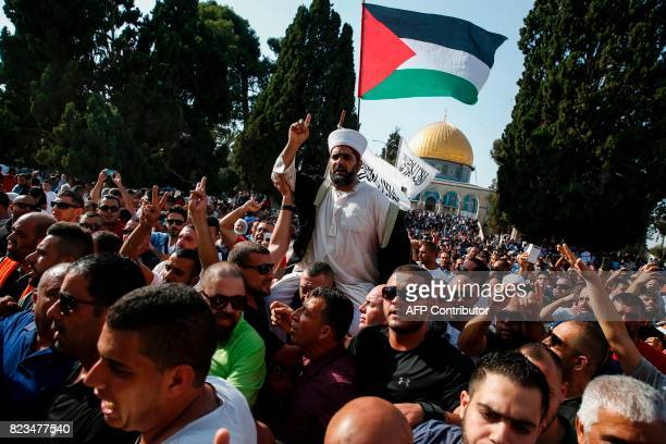 TOPSHOT Palestinians carry the director of AlAqsa mosque Sheikh Omar Kiswani on their shoulders as they shout slogans and wave a national flag upon...