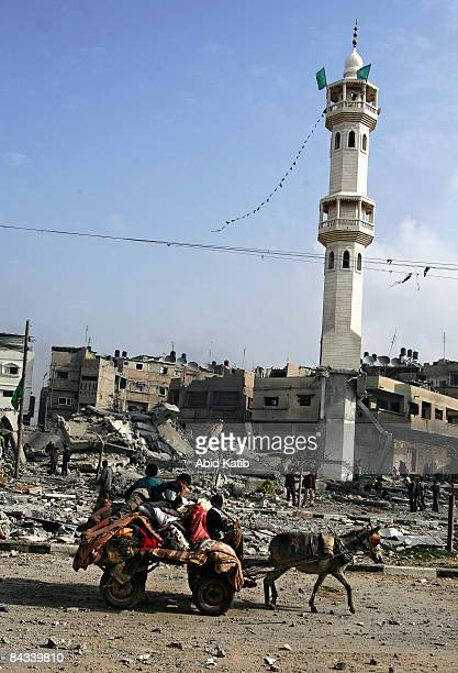 Palestinians carry their belongings on a donkey cart as they leave the area while they pass by the rubble of the Taha mosque after it was struck by...