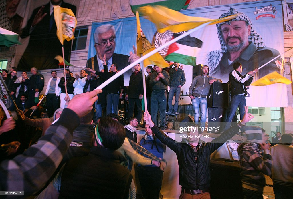 Palestinians celebrate in front of portraits of Palestinian Authority leader Mahmoud Abbas (B-L) and late Palestinian leader Yasser Arafat in the West Bank city of Hebron on late November 29, 2012, after the General Assembly voted to recognise Palestine as a non-member state. The UN General Assembly voted overwhelmingly to recognize Palestine as a non-member state, giving a major diplomatic triumph to president Mahmud Abbas despite fierce opposition from the United States and Israel. AFP PHOTO / HAZEM BADER