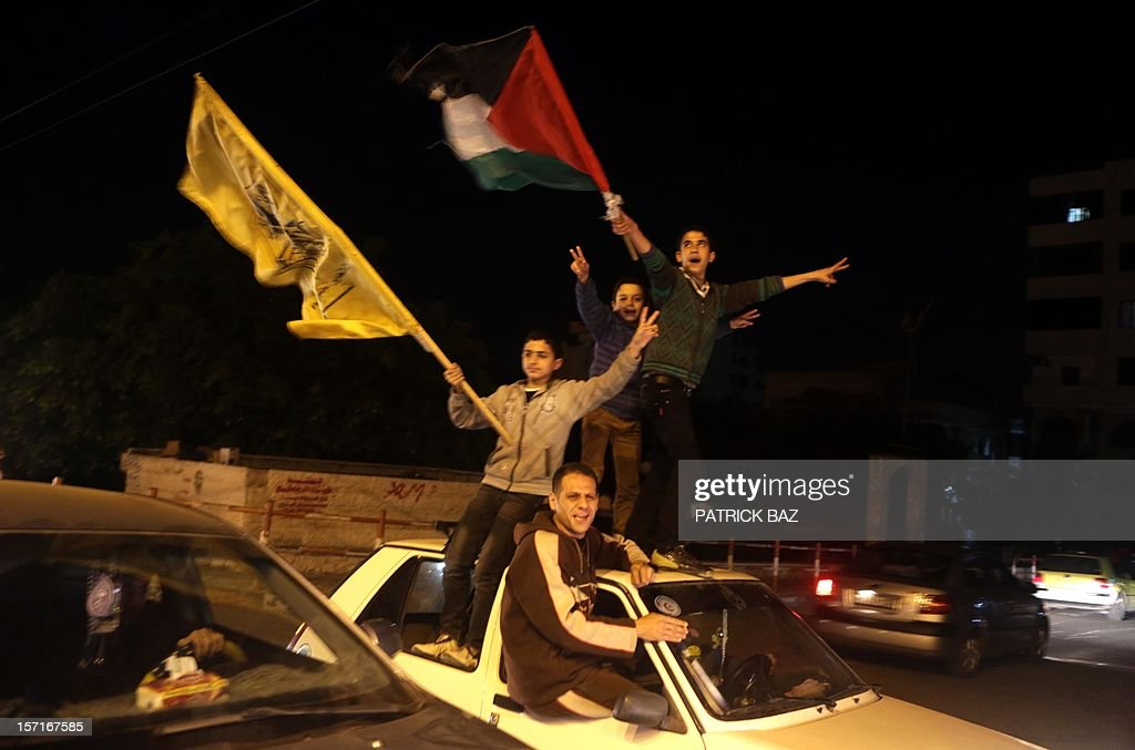 Palestinians celebrate in Gaza City early on November 30, 2012, after the UN General Assembly voted to upgrade them to a non-member state observer. The UN General Assembly on Thursday voted overwhelmingly to recognize Palestine as a non-member state, triggering scenes of joy on the streets of the Israeli-occupied West Bank. In a major defeat for the United States and Israel, Palestinian president Mahmud Abbas won what he called a 'birth certificate' for a Palestinian state, with the backing of 138 countries in the 193 member assembly. AFP PHOTO / PATRICK BAZ