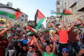 Palestinians celebrate in the West Bank city of Ramallah on May 30 after Palestine qualified for their maiden Asian Cup appearance with a 10 win over...