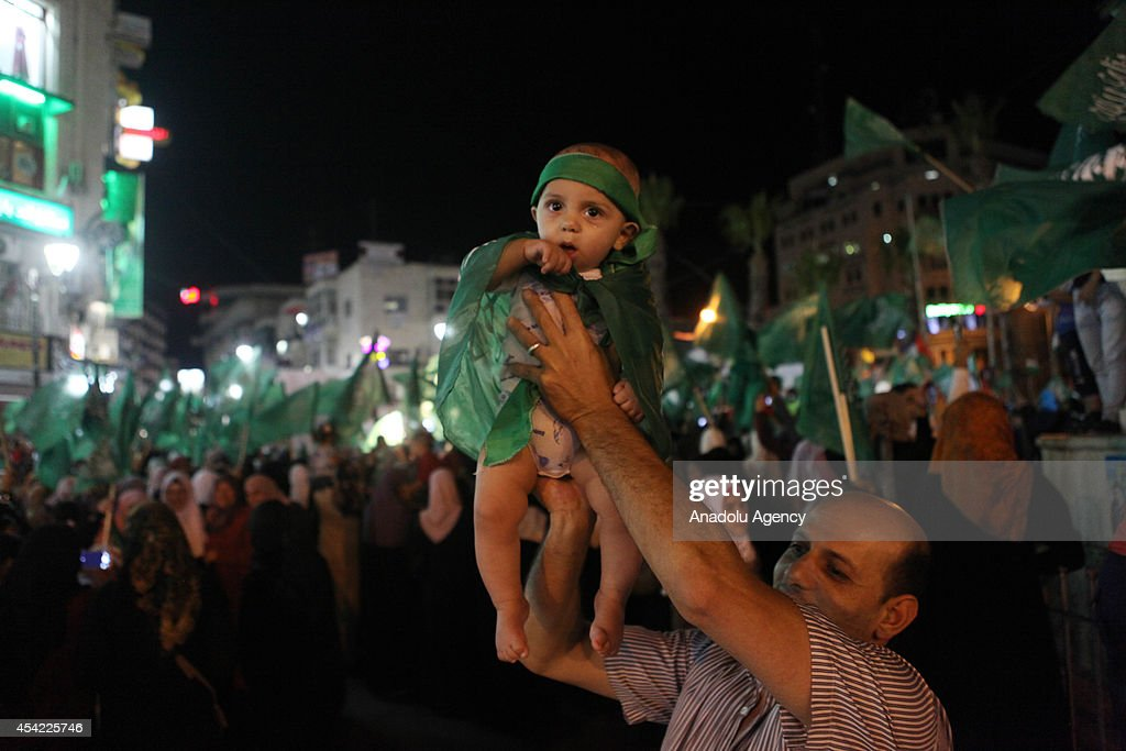 Palestinians celebrate the ceasefire between Palestinian resistance factions and Israel on August 26, 2014 in Ramallah, West Bank. An Egyptian-brokered ceasefire went into effect on August 26, 2014, bringing to a halt 51 days of attacks. The ceasefire deal includes the opening of all border crossings between the Gaza Strip and Israel, which would effectively signal the end of Israel's years-long embargo of the coastal enclave.