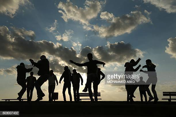 TOPSHOT Palestinians celebrate the last day of the year at the sea port in Gaza City on December 31 2015 AFP PHOTO / MOHAMMED ABED / AFP / MOHAMMED...