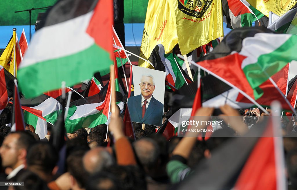 Palestinians celebrate waving their national flag as Palestinian president Mahmud Abbas (portrait) delivers a speech to the crowd upon his arrival in the West Bank city of Ramallah on December 2, 2012, after winning upgraded United Nations status for the Palestinians earlier in the week. Abbas said 'Palestine has accomplished a historic achievement at the UN,' three days after the United Nations General Assembly granted the Palestinians non-member state observer status in a 138-9 vote.
