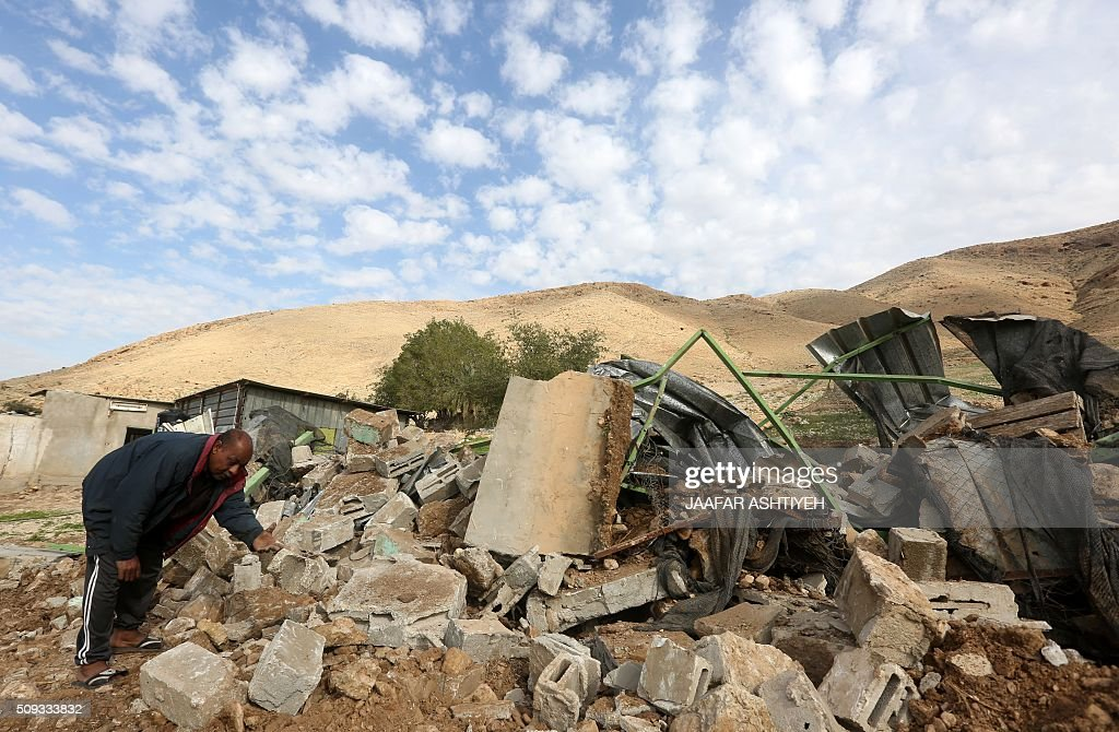 Palestinians check the rubble of their house after it was demolished by Israeli authorities on February 10, 2016 in the West Bank village of Jeftlek, in the Jordan valley near Jericho Israel often demolishes buildings constructed without the required Israeli permits in Area C of the West Bank, which is under full Israeli control. / AFP / JAAFAR ASHTIYEH
