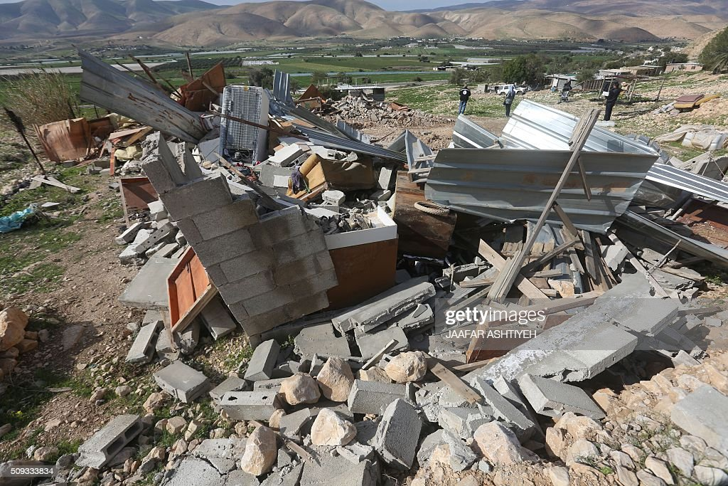 Palestinians check the rubble of their house after it was demolished by Israeli authorities on February 10, 2016 in the West Bank village of Jeftlek, in the Jordan valley near Jericho. Israel often demolishes buildings constructed without the required Israeli permits in Area C of the West Bank, which is under full Israeli control. / AFP / JAAFAR ASHTIYEH