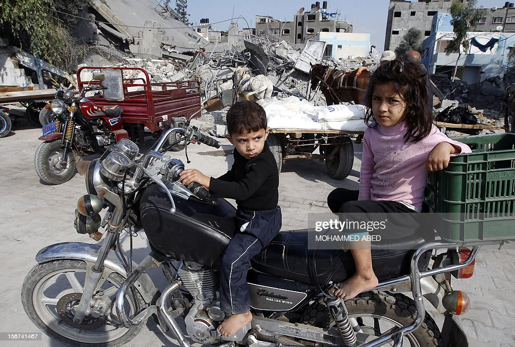 Palestinians children sit on a motor bike outside a UN supplies center after it was damaged in an Israeli airstrike directed at the nearby Hamas police headquarters at the Jabalya refugee camp, in the northern Gaza Strip on November 20, 2012. Israel halted a threatened Gaza ground offensive to give Egyptian-led truce talks a chance as top diplomats flew in to boost efforts to end nearly a week of cross-border violence. AFP PHOTO/MOHAMMED ABED