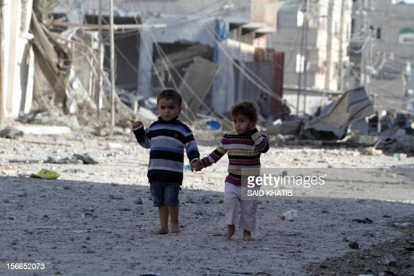Palestinians children walk past destroyed buildings following Israeli air strikes on the southern Gaza Strip town of Rafah on November 18 2012...