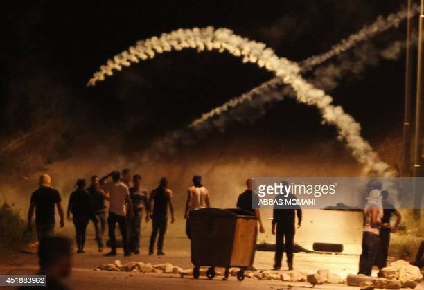 Palestinians clash with Israeli soldiers at the gates of the Beit El Jewish settlement in the Israel occupied West Bank near Ramallah on July 9 as...