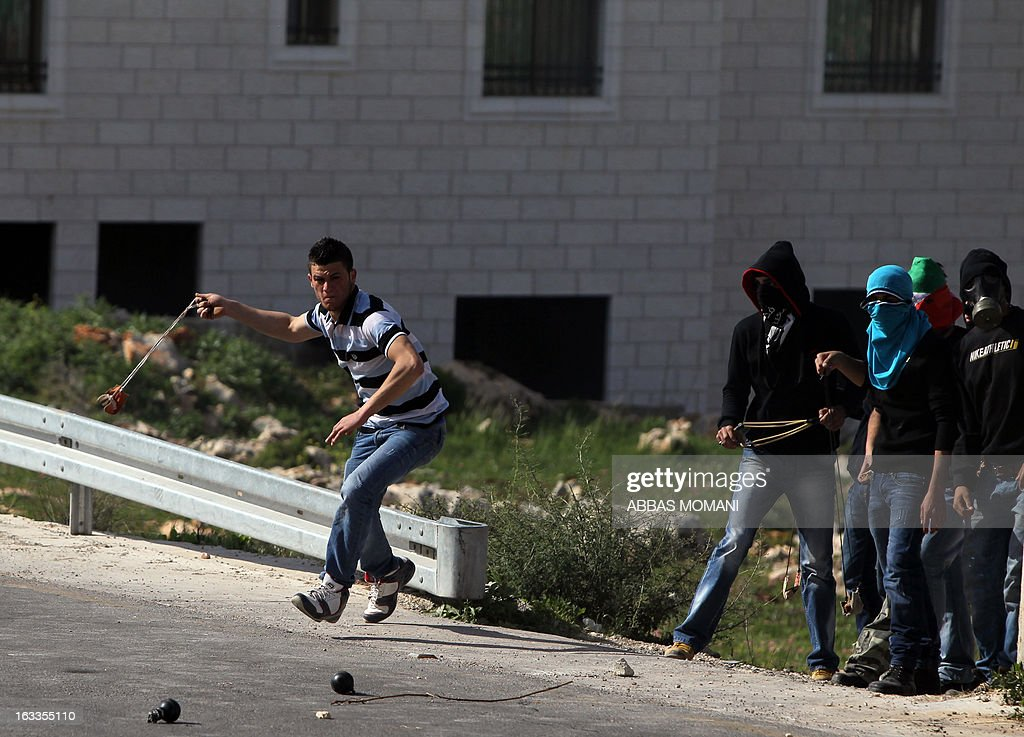 Palestinians clash with Israeli soldiers following the funeral of Mohammad Asfour, a 22-year-old protester who died of wounds sustained the previous day, in the West Bank village of Abud on March 8, 2013. Asfour was wounded in the head by a rubber-coated steel bullet fired by Israeli troops during a protest which erupted after a prisoner died in Israeli custody.