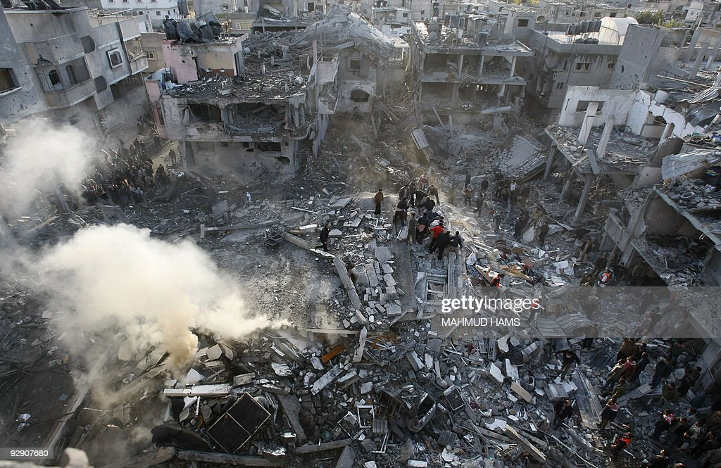 Palestinians climb on the rubble to inspect the damage at the destroyed house of Hamas leader of Nizar Rayan following an Israeli air strike in Jabalia in the northern Gaza Strip on January 1, 2009. Rayan was killed today with his four wives and two of his children in an Israeli air strike in Gaza, medics said. Rayan, a hardliner within the Islamist group, was killed when a missile crashed into a five-storey house that he shared with his wives and children in Jabalia in the north of the territory, the medics said. AFP PHOTO/MAHMUD HAMS