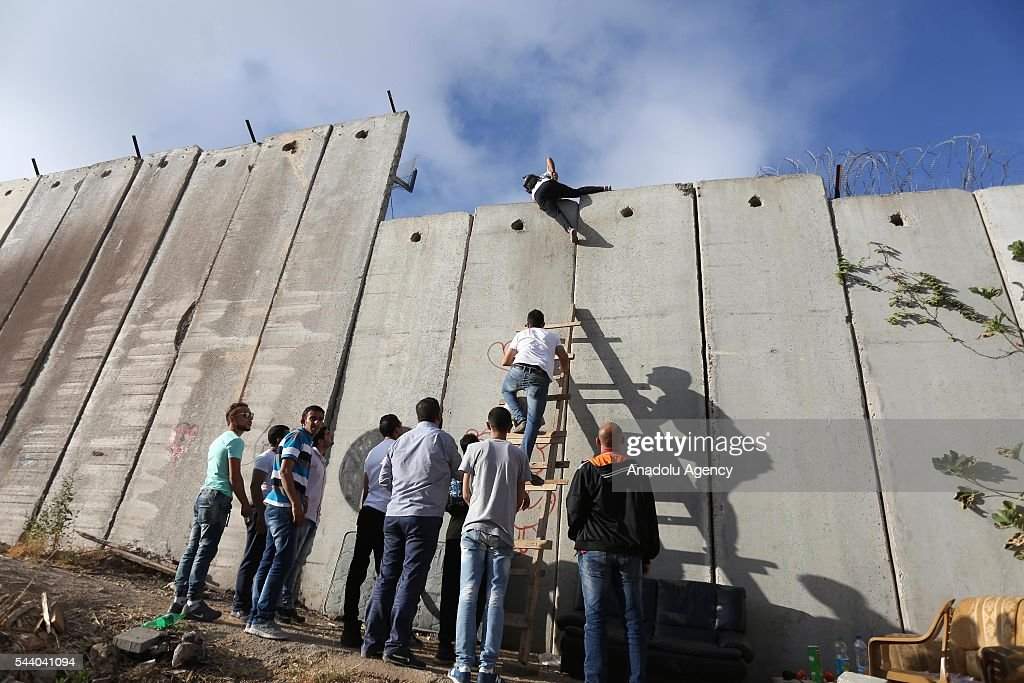 Palestinians climb on the separation wall in the town of Al-Ram to cross into Jerusalem to attend the last Friday Prayers of the Ramadan at Al-Aqsa Mosque on July 1, 2016.