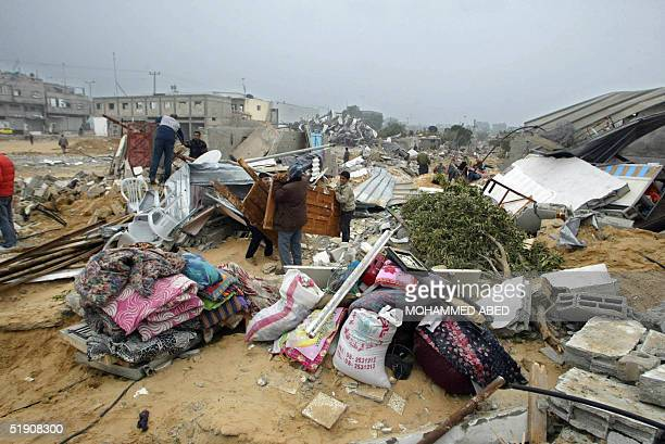 Palestinians collect belongings saved from the rubble of their houses after Israeli troops withdrew from a section of the Khan Yunis refugee camp in...