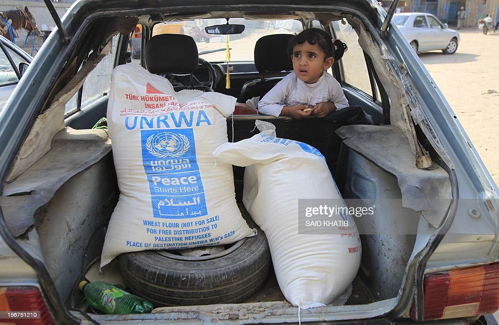 Palestinians collect food supplies from the United Nations Relief and Works Agency (UNRWA) headquarters in Rafah in the southern Gaza Strip on November 20, 2012. A group of 38 aid agencies urged the international community to take action to secure a ceasefire in Gaza to prevent 'another widespread humanitarian disaster.' AFP PHOTO/ SAID KHATIB